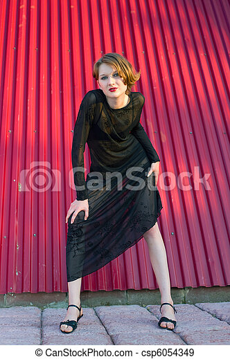 girl in black dress against red wall - csp6054349