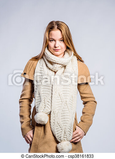 Girl in brown coat and knitted scarf, studio shot - csp38161833
