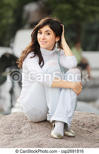 Girl in casual sitting on stone - csp2691816