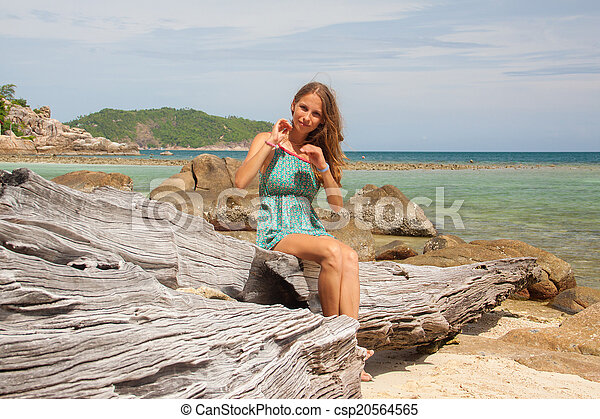 girl in dress sitting on a rock by the sea - csp20564565
