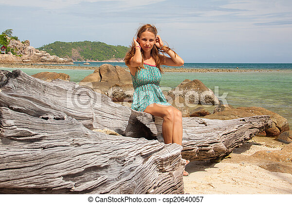 girl in dress sitting on a rock by the sea - csp20640057