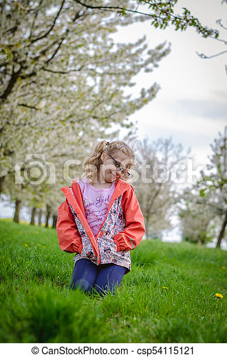 girl in grass in springtime sitting in the grass - csp54115121