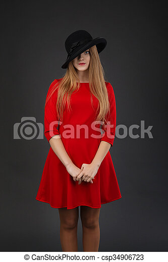 girl in red dress and black hat. - csp34906723