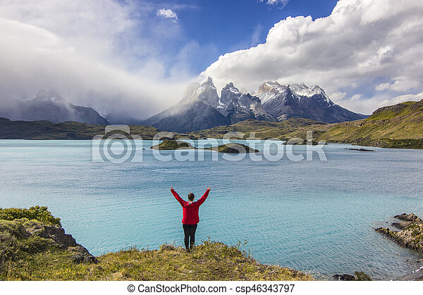 girl in red jacket with hands up standing above lake in mountains - csp46343797