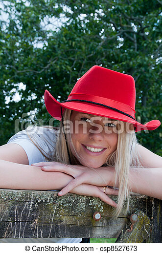 adb3e8d0701 Girl in red stetson hat. Country farm giel leaning on a gate wearing ...