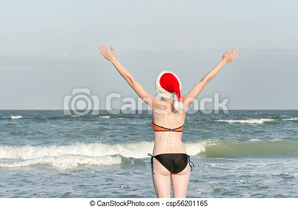 9caa1d289ec ... View Stock Photo. Girl in Santa hats with the inscription New Year on  the back. Sea shore.
