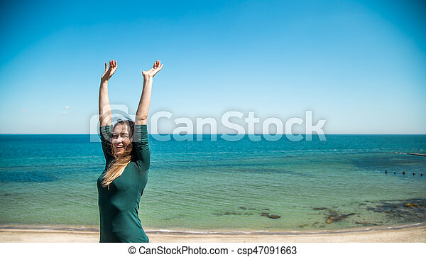 Girl in sportswear fitness by the sea listening