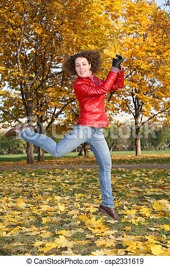 girl in the red jacket jumps in the park in autumn - csp2331619