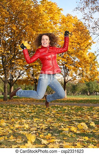 girl in the red jacket jumps in the park in autumn 2 - csp2331623