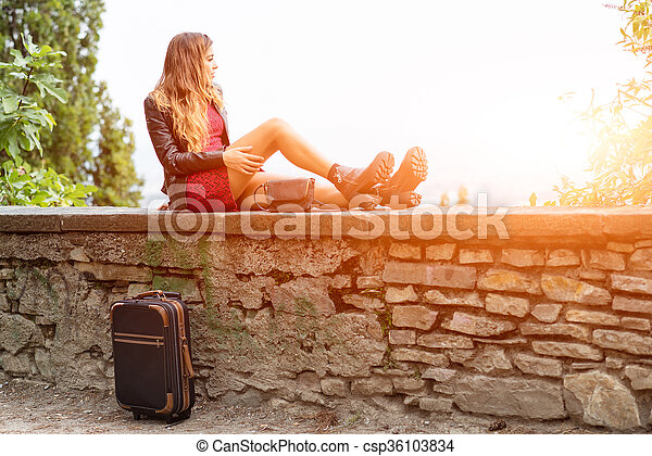 Girl in the sun on a wall with suitcase waiting. - csp36103834
