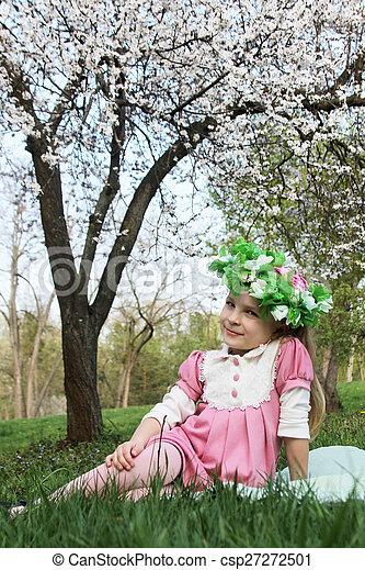 Girl in wreath sitting under spring tree - csp27272501