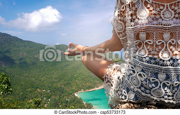 girl in yoga pose with picturesque view of the island at a height - csp53733173