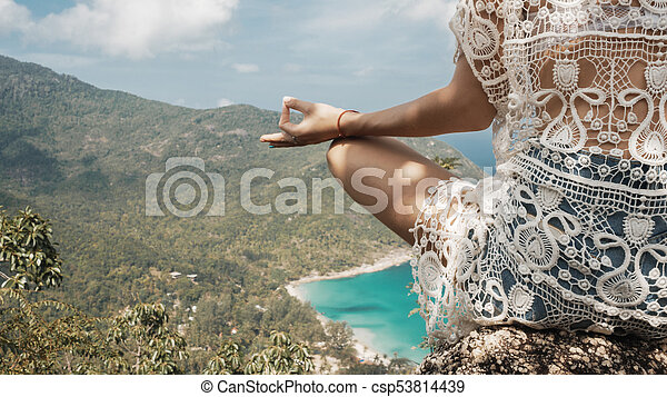 girl in yoga pose with picturesque view of the island at a height - csp53814439