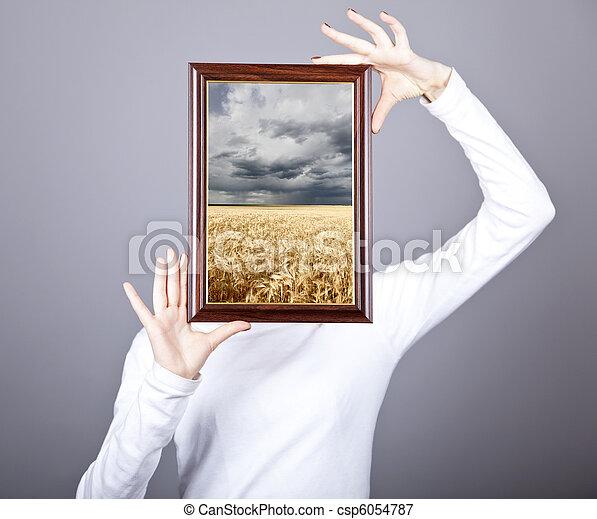 Girl keep frame with wheat field and rain inside. - csp6054787