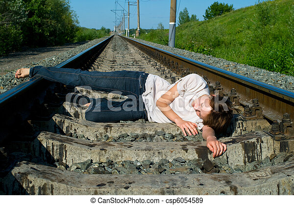 girl laying on a railway - csp6054589