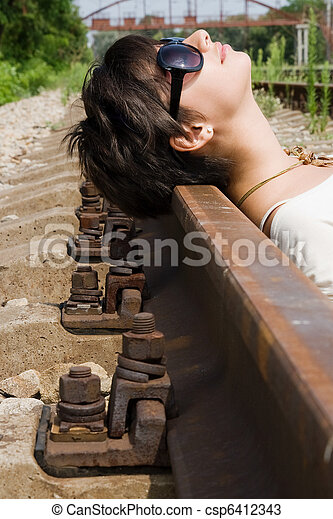 Girl laying on the railroad carelessly - csp6412343