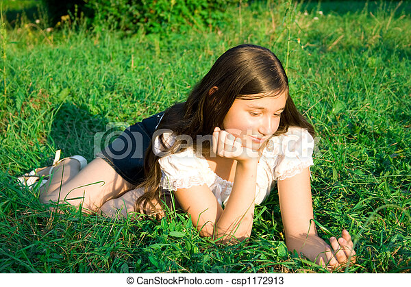 girl lays on a grass - csp1172913
