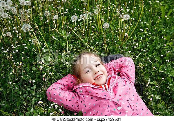 Girl lying in grass, surrounded by dandelion - csp27429501