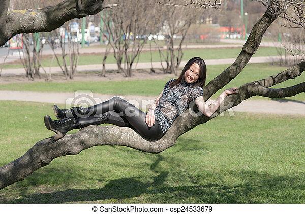 girl lying on a tree branch - csp24533679