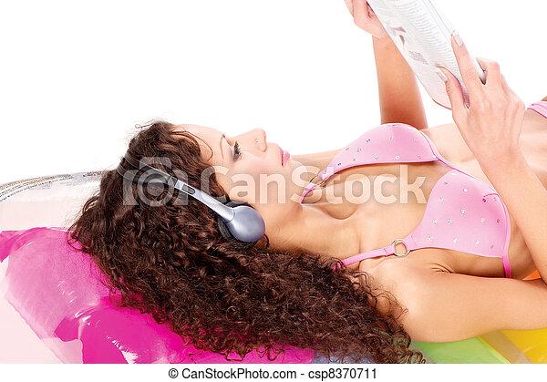 girl on air mattress reading newspaper - csp8370711