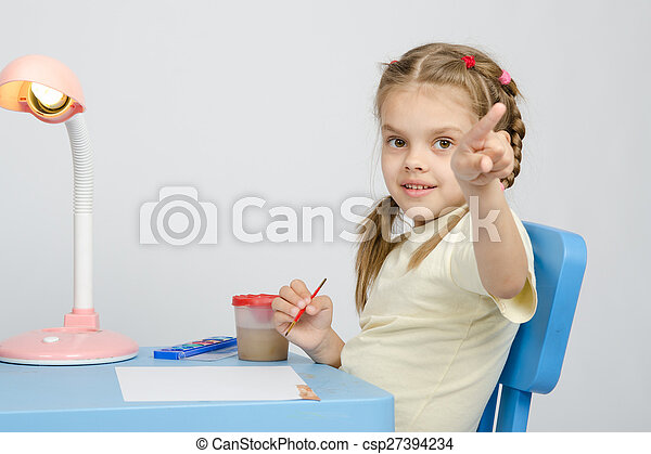 Girl painting paints at table, points the finger - csp27394234