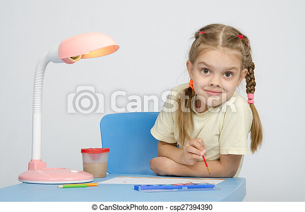 Girl painting paints at the table, looked into frame - csp27394390
