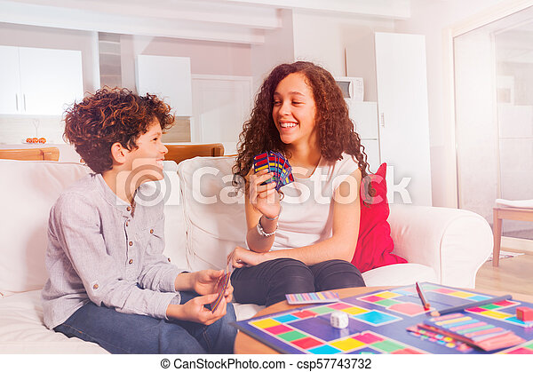 Girl playing card games with her younger brother - csp57743732