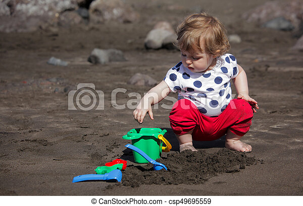 Girl playing on the beach with volcanic sand - csp49695559