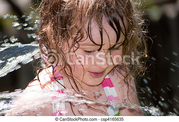 Girl playing outside with water on the summer - csp4165635