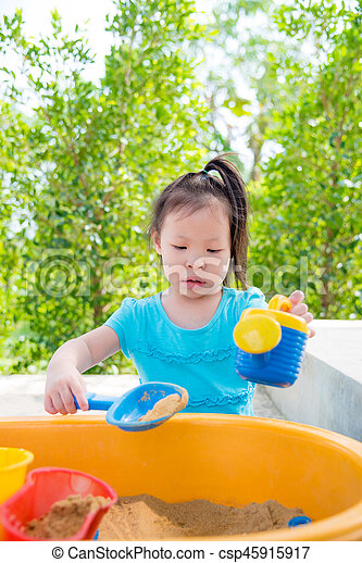 girl playing sand in sand box - csp45915917