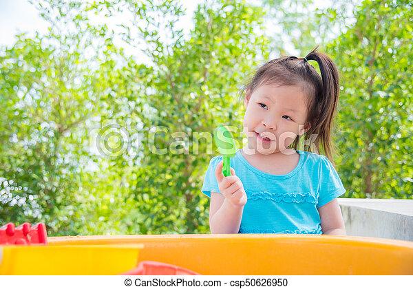 girl playing sand in sandbox - csp50626950