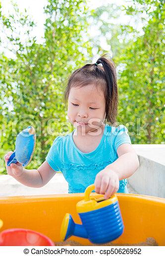 girl playing sand in sandbox - csp50626952