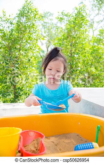 girl playing sand in sandbox - csp50626954