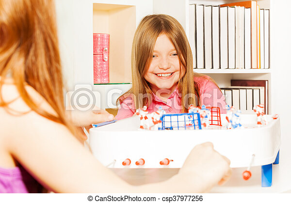 Girl playing table board hockey with her friend - csp37977256