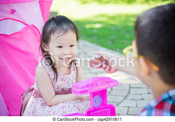 girl playing with her brother in park - csp42910611