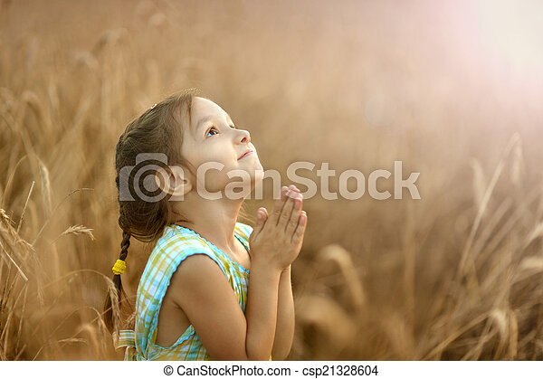 Girl prays in wheat field - csp21328604