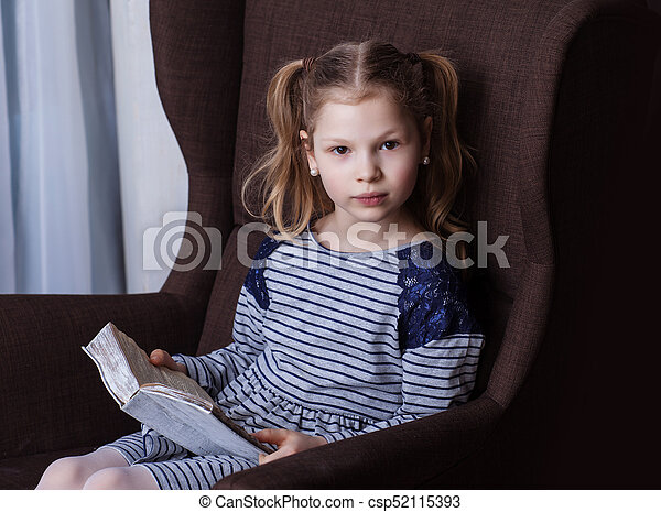 Girl reading a book in a chair - csp52115393