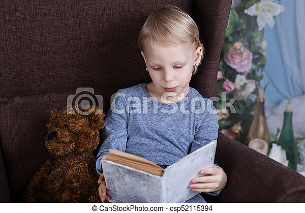 Girl reading a book in a chair - csp52115394
