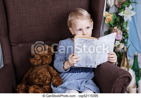 Girl reading a book in a chair - csp52115395
