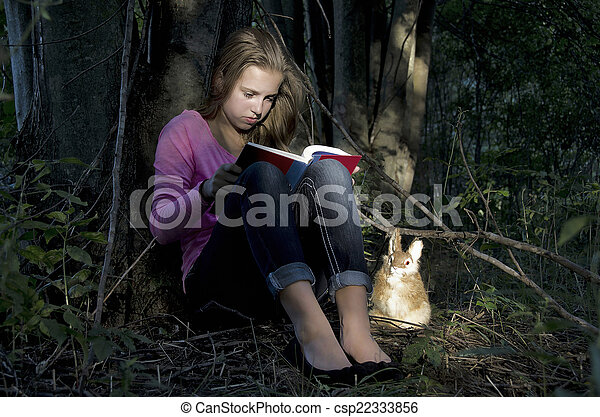 girl reading a book in woods - csp22333856