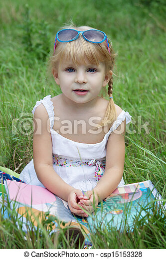 Girl reading book and sitting in grass - csp15153328