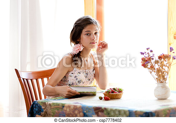 Girl reading book sitting at table indoor in summer day with str - csp7778402