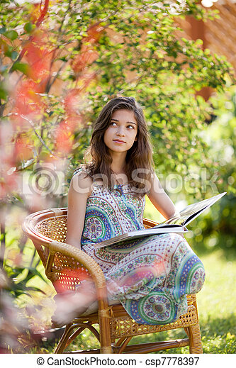 Girl reading book sitting in wicker chair outdoor in summer day - csp7778397