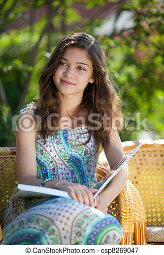 Girl reading book sitting in wicker chair outdoor in summer day - csp8269047