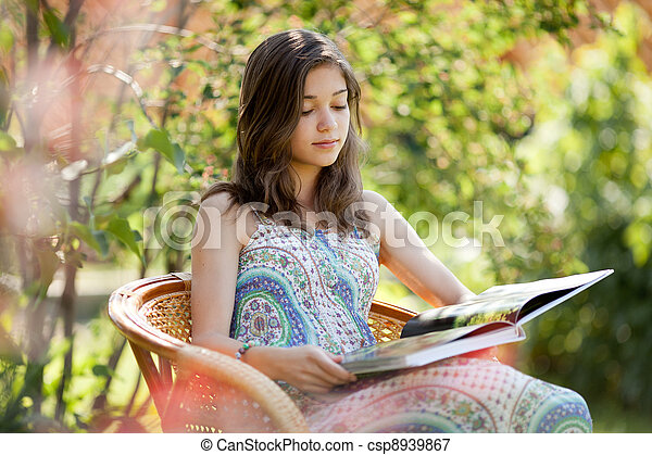 Girl reading book sitting in wicker chair outdoor in summer day - csp8939867