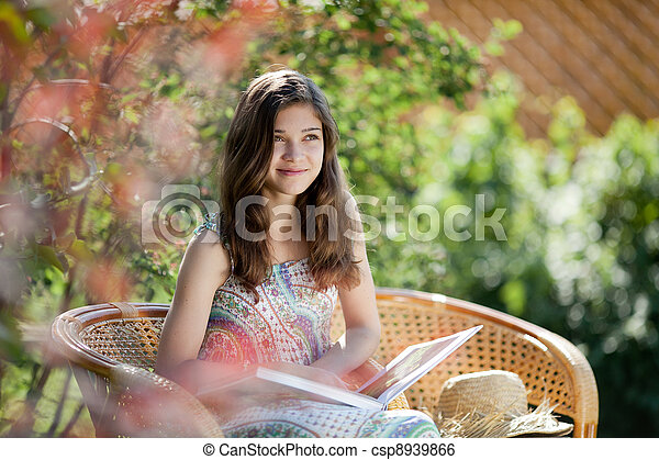 Girl reading book sitting in wicker chair outdoor in summer day - csp8939866
