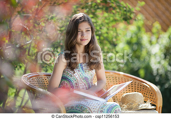 Girl reading book sitting in wicker chair outdoor in summer day - csp11256153