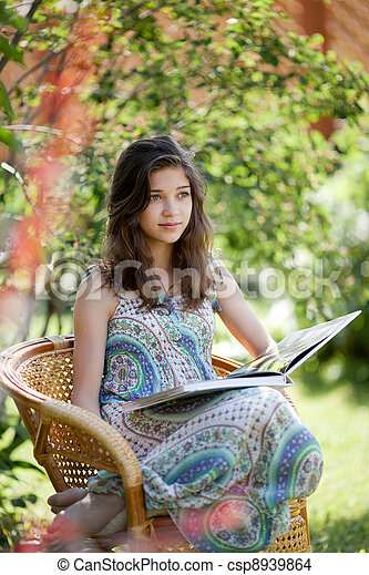 Girl reading book sitting in wicker chair outdoor in summer day - csp8939864