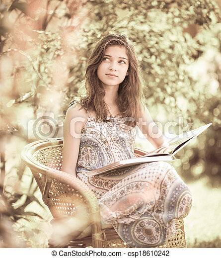 Girl reading book sitting outdoor in summer day. Retro stylized photo. - csp18610242