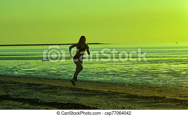 girl running by the sea on the beach - csp77064042